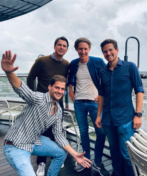 four men standing on a boat
